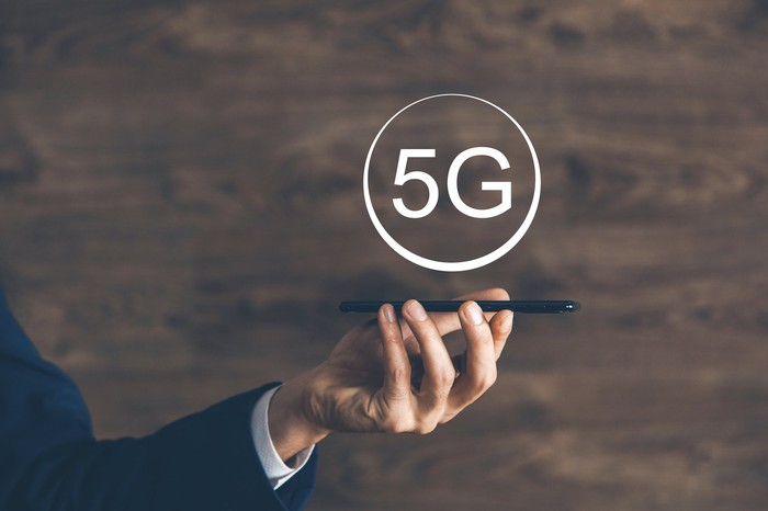 Person holding a smartphone with the word 5G above it.