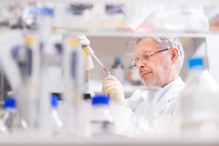 Scientist in a lab injecting something into a test tube, which bottles of  liquid on shelves surrounding him.