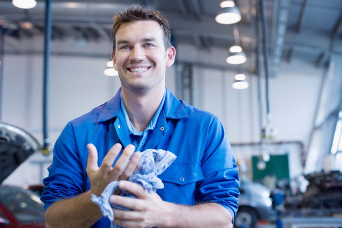 An auto repair worker in blue workwear smiles during a break.