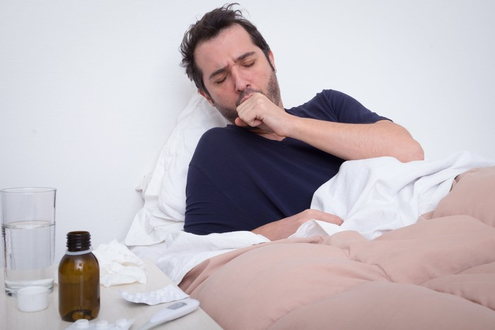 Man coughing in bed with cough medicine, a thermometer, and a glass of water on his end table.