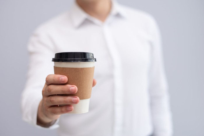 Man wearing white shirt, extending coffee in a to-go cup.