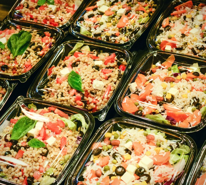 Photograph of pre-packaged meal salads in grocery store cooler.