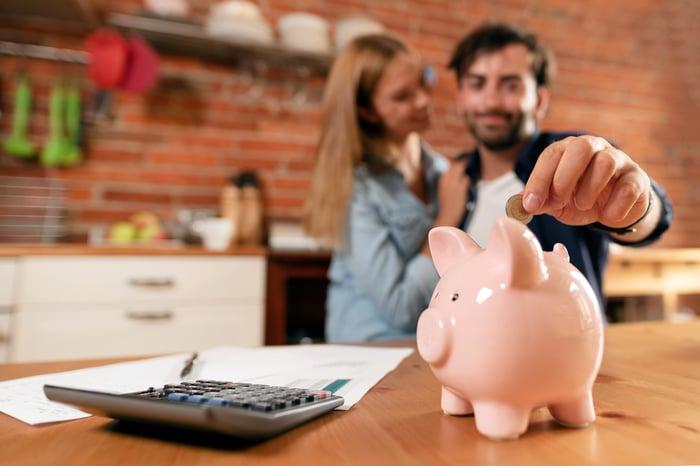 Man putting money into a piggy bank.