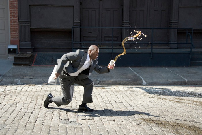 A businessman stumbling and spilling his drink.
