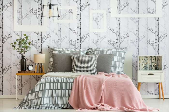 A bedroom including a bed with several pillows, two nightstands, and leafy wallpaper.