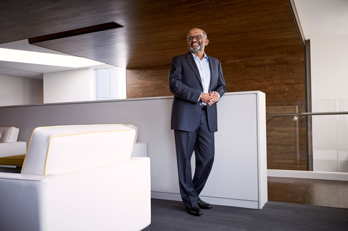 Adobe CEO Shantanu Narayen standing and smiling in the company's headquarters office.