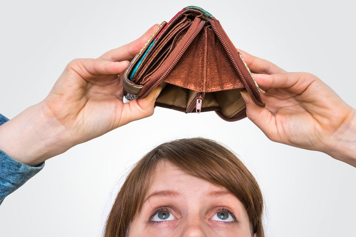 A woman looks up at an open and empty wallet she's holding over her head.