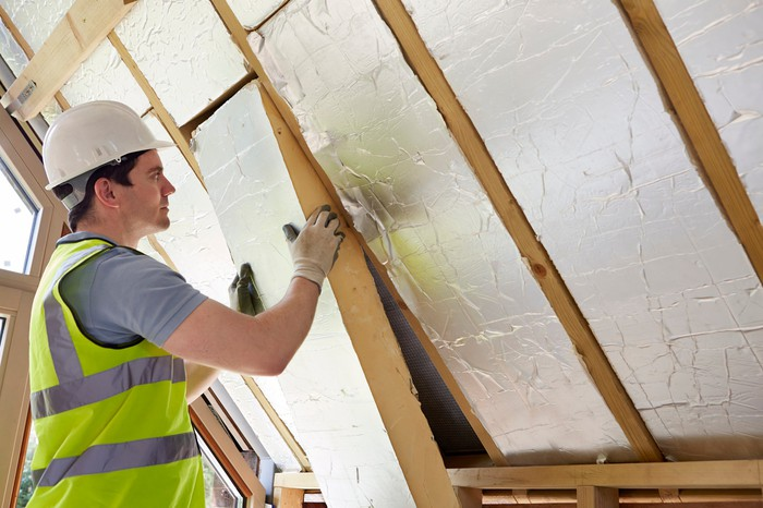 A builder fits insulation into a customer's roof.