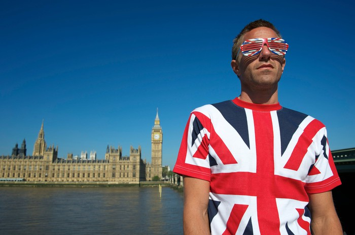 A young man wearing a British-themed shirt and glasses in front of Parliament.