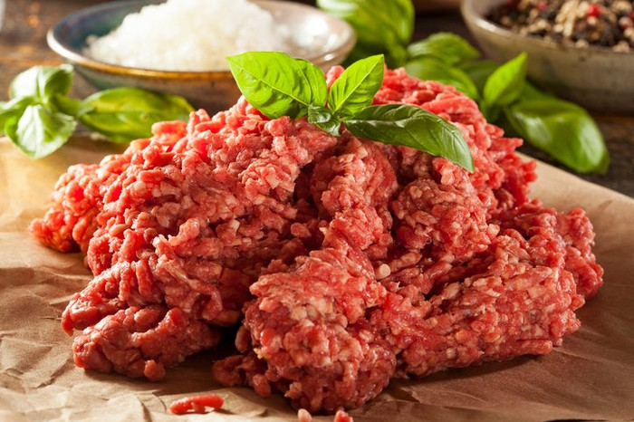 Ground beef with basil leaves on it