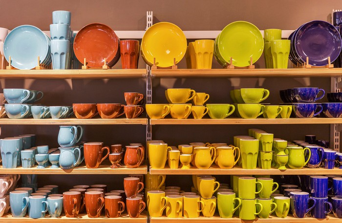 Plates and bowls displayed by color on a wall of shelving