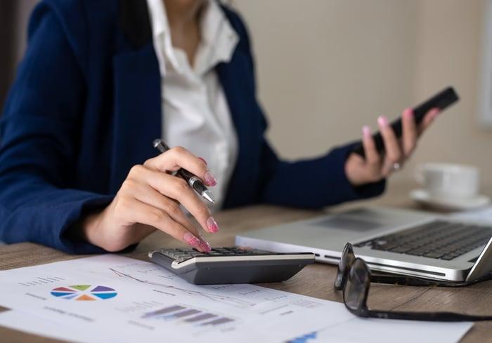A woman in a suit sits at a desk in front of a laptop, using a calculator.