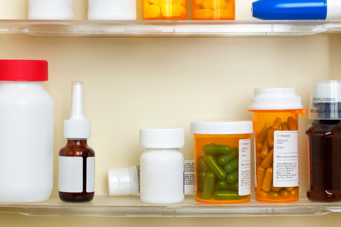 A medicine cabinet shelf with various bottles of prescription medications sitting on it.