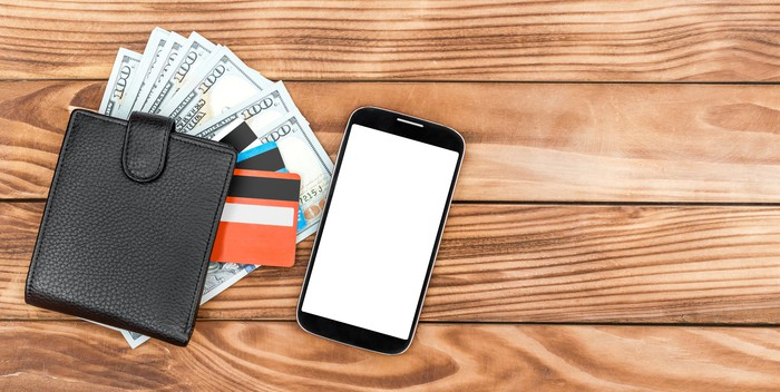 A wallet with cash and credit cards splayed out lying next to a smartphone.