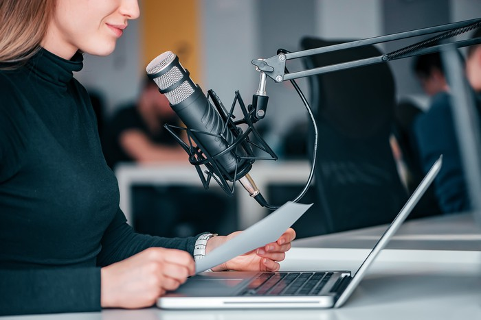 Woman reading into a microphone while creating a podcast