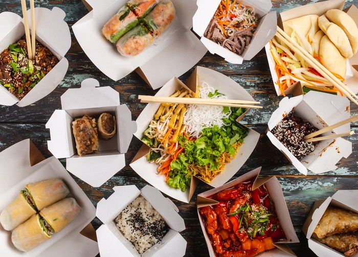 Various types of Asian food in 11 takeout boxes