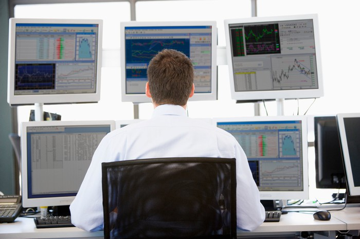 A man looks like at five computer screens showing stock movement