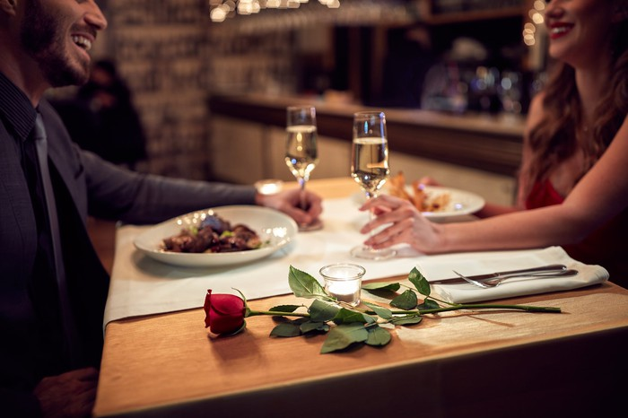 Man and woman eating dinner at restaurant table with wine glasses in their hands.