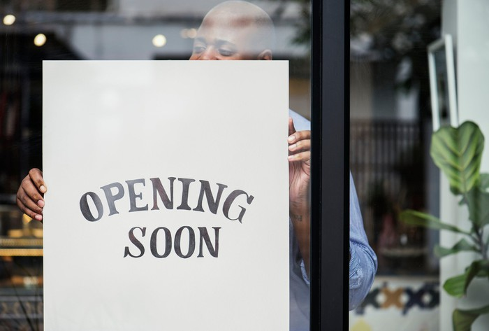 Man hanging sign that says opening soon.