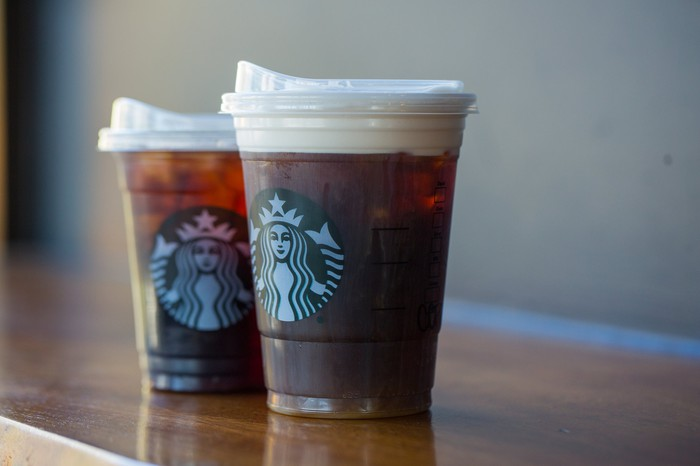 Two Starbucks cold drink cups with strawless lids.