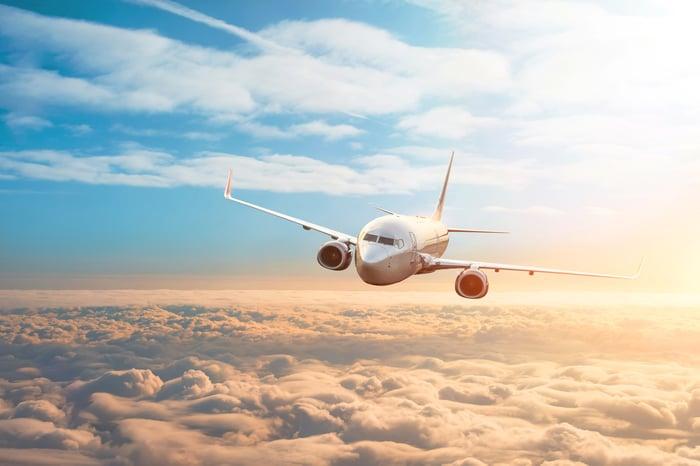 A passenger plane flies over a sunset sky.