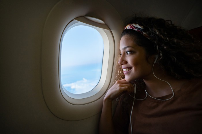 A woman gazes out the window of an airplane.