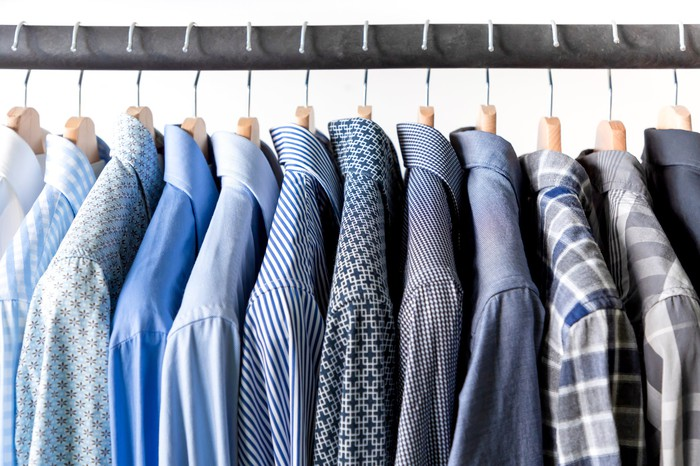 Dress shirts in various shades of blue and gray hang on a rack.