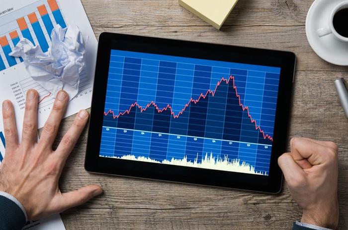A man pounds his fist on a table next to a crumpled piece of paper and a tablet showing a declining stock chart.