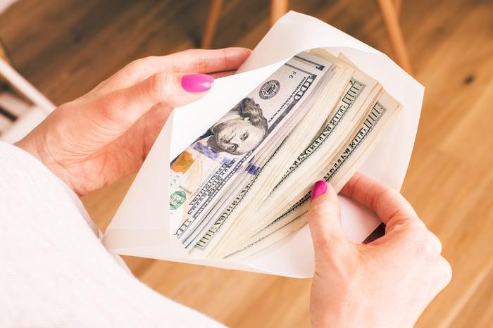 Older woman holding envelope full of $100 bills.