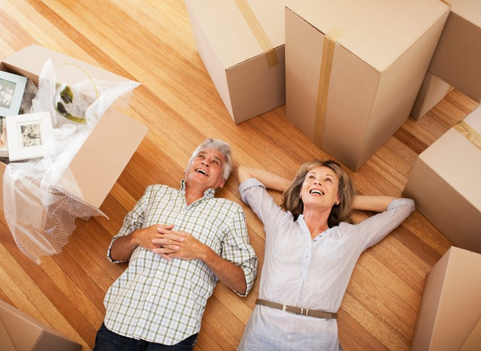 Older couple laying on floor in the middle of moving boxes.