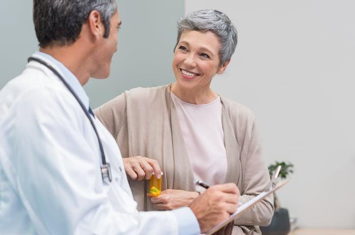 Doctor talking to smiling older woman.