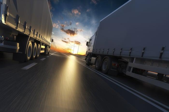 Two trucks driving at dawn