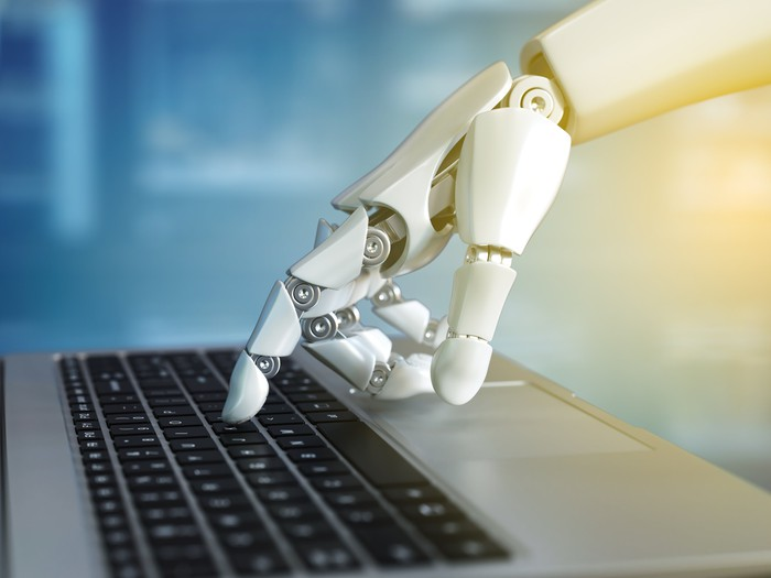 Robot hand touching a keyboard.