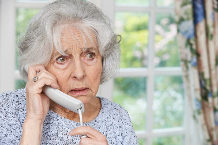 Older woman with concerned expression talking on phone
