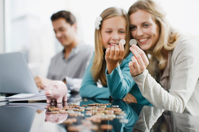 A young mother smiles and holds up coins with her daughter next to a piggy bank at a table while Dad operates his laptop behind them out of focus.
