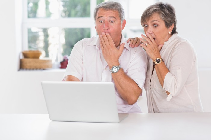 Older man and woman at laptop, covering their mouths as if in shock