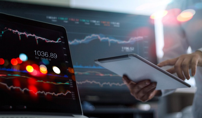 A man holding a tablet computer with computer screens displaying stock charts in the background.