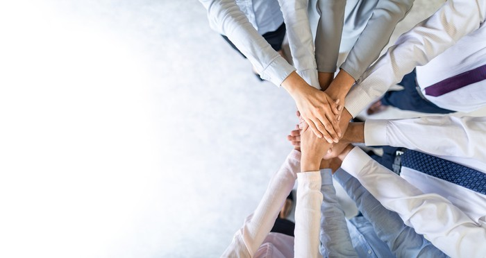 Photograph of business team putting their hands together, like a sports team starts a game.