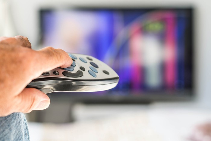 closeup of a hand pressing a remore control pointing it at a television out of focus in the background.