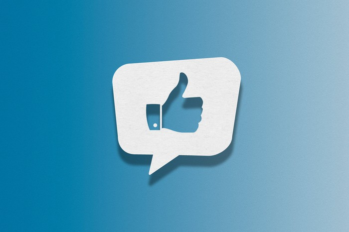 White speech bubble with a blue thumbs up on a blue background.