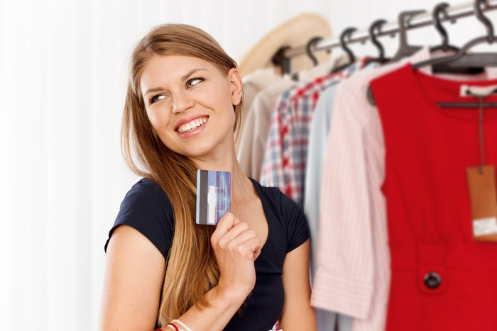 A smiling young woman holding up a credit card while standing next to a clothing rack.