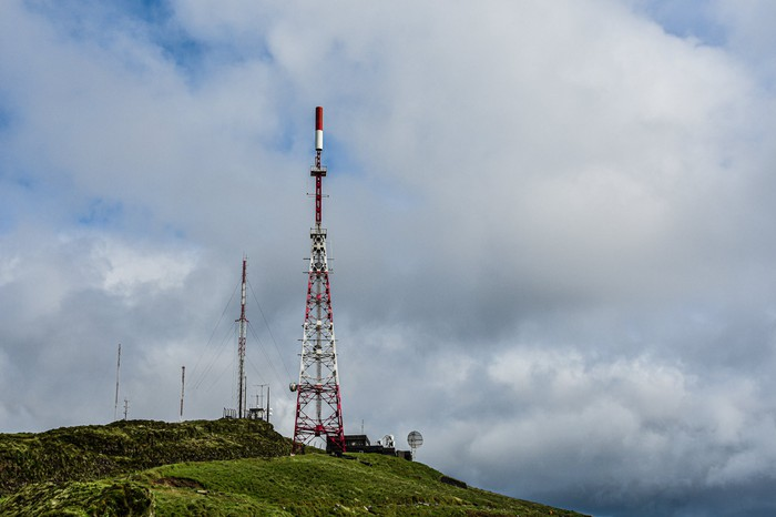 Several cell towers stand atop a green hill.