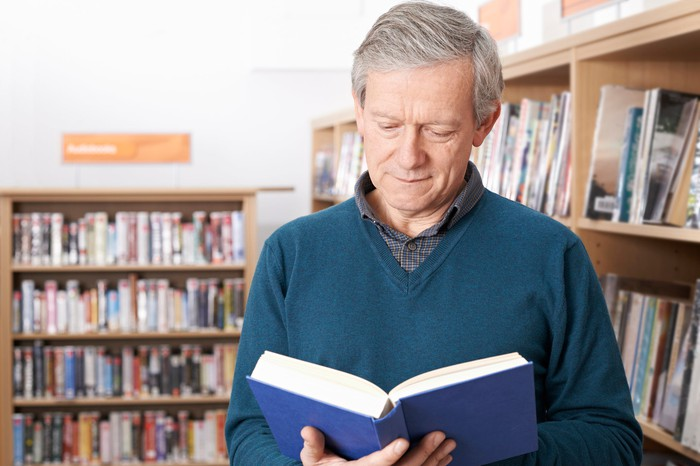 Older man looking at an open book in front of bookshelves