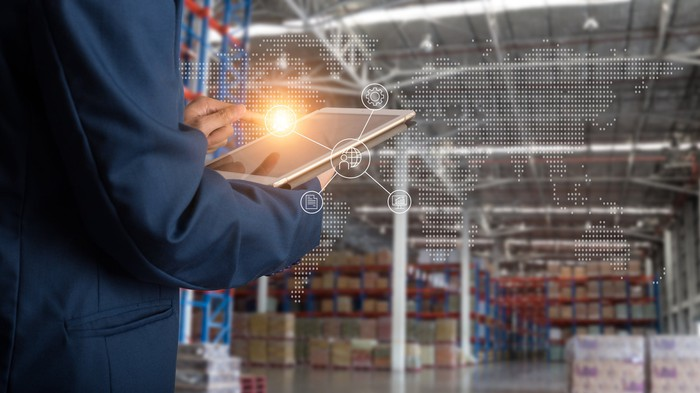 Shot from behind a man holding a tablet in a modern warehouse and a light illuminates from the tablet.