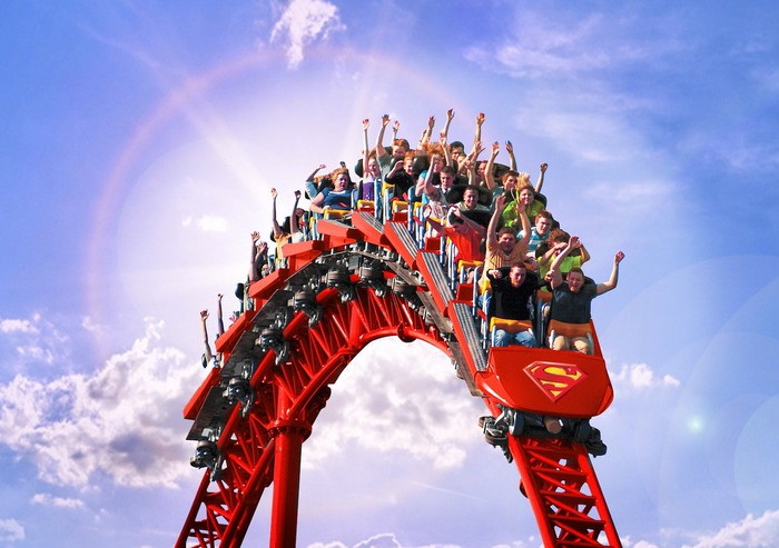 Riders on the Superman coaster at Six Flags going over a hill.