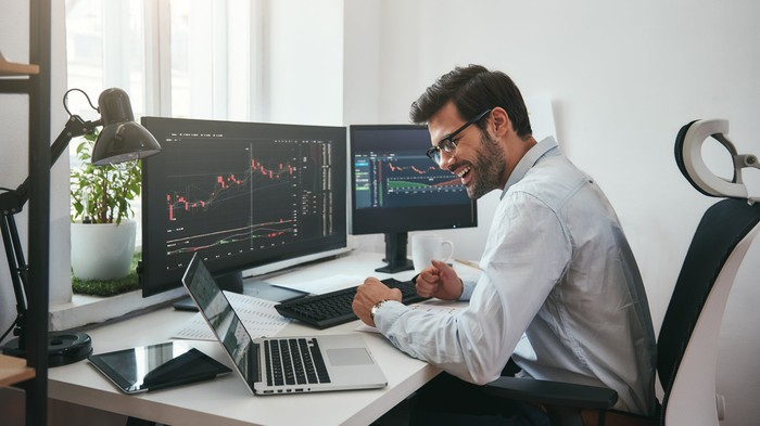 A man sits at a desk in front of two monitors displaying financial data, as he looks smiling at a laptop screen.