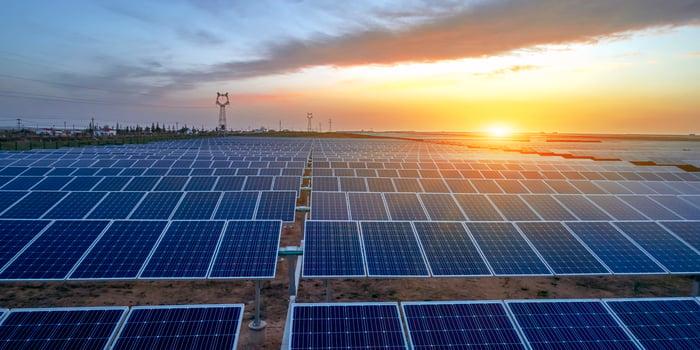 A solar energy facility at sunset.