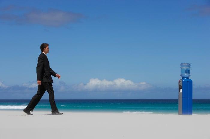 A man on a beach walks toward a water dispenser