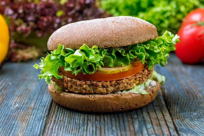 A veggie burger with lettuce and tomato sits on a wooden surface.