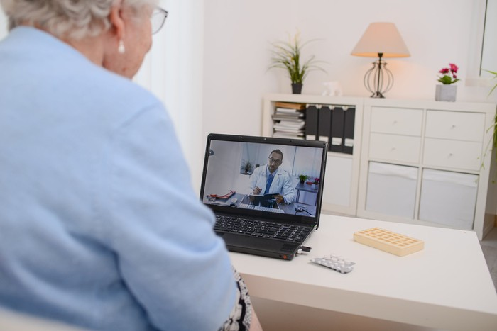 An elderly woman videoconferencing with a doctor on a laptop.